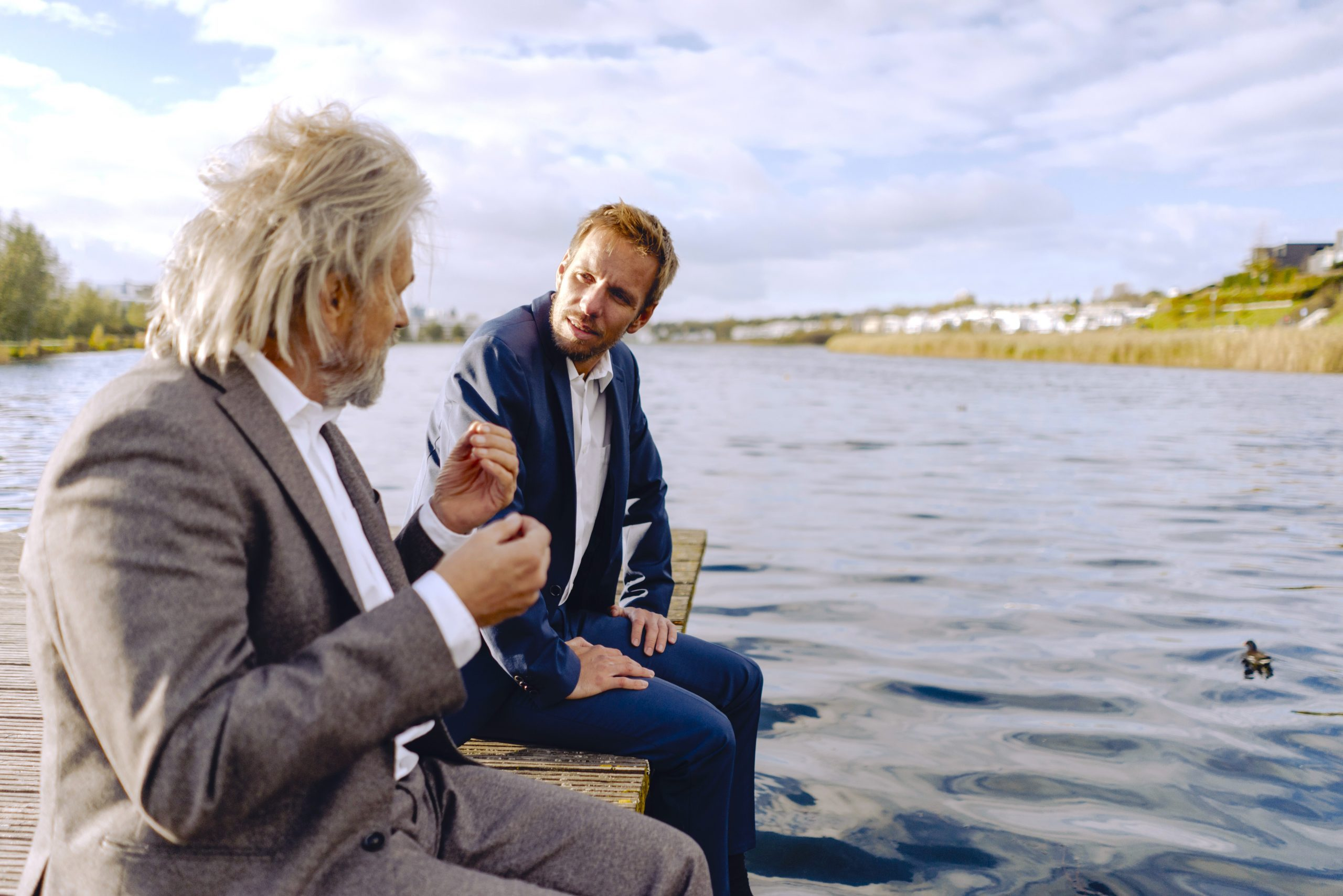 Two businessmen sitting on jetty at a lake talking